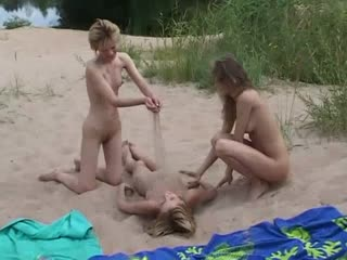 Three sand playing beach nudists